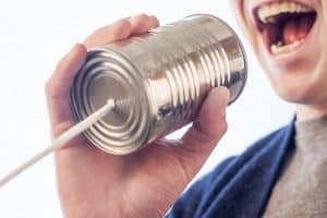 "Picture of person talking into a ""can phone"" to illustrate customer reviews article"